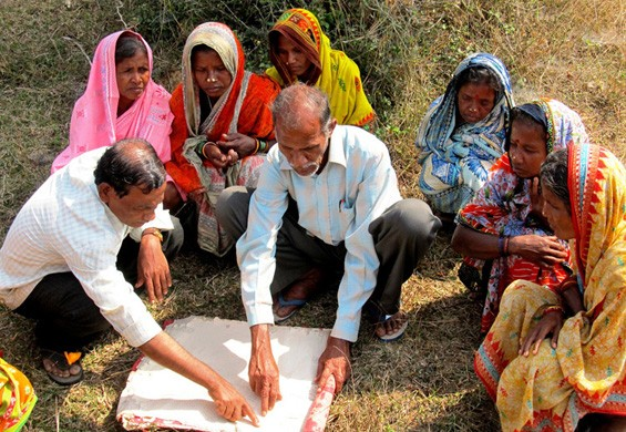Women with government officials showing their new land plots